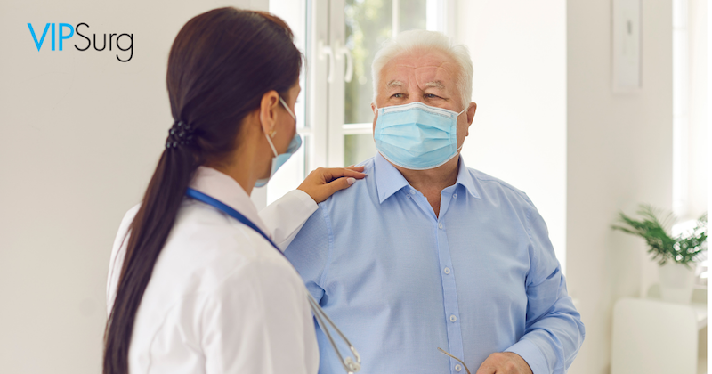 Female Doctor hand on patient and talking to an older male patient with a mask on in a blue button down shirt