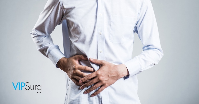 Man in dress shirt holds hands on lower abdomen to relieve abdominal pain he has been avoiding treatment for. VIPSurg Las Vegas logo at bottoms left corner.