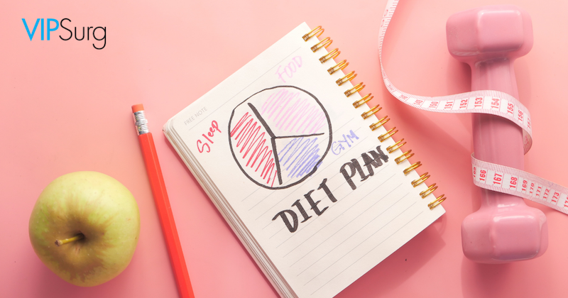 Green apple, red pencil, diet plan notepad, pink dumbbell, and pink measuring tape on light pink background